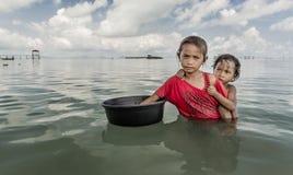 Bajau plemienia małej dziewczynki mienia zbiornik i zbliżająca się turystyczna łódź dla pytać jedzenie jeść, Sabah Semporna, Male Fotografia Stock