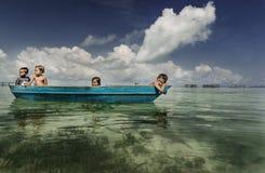 Bajau-Stammkinder, die Spaß durch das Rudern des kleinen Bootes nahe ihren Dorfhäusern im Meer, Sabah Semporna, Malaysia haben stockbild