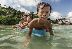 Bajau-Stammkinder, die Spaß durch das Rudern des kleinen Bootes nahe ihren Dorfhäusern im Meer, Sabah Semporna, Malaysia haben lizenzfreie stockfotos