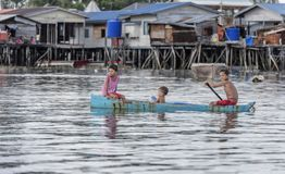 Bajau-Stammkinder, die Spaß durch das Rudern des kleinen Bootes nahe ihren Dorfhäusern im Meer, Sabah Semporna, Malaysia haben Stockfoto