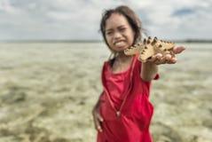 Bajau-Stammmädchen hob Sternfische vom Meer und das Versuchen auf, das an Touristen, Sabah Semporna, Malaysia zu verkaufen Lizenzfreie Stockfotos