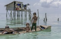 Bajau tribal kids having fun by jumping into sea from their boat, Sabah Semporna, Malaysia stock images