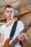Bajista con el tatuaje que se coloca con su guitarra Foto de archivo