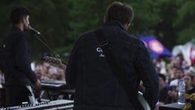 Bajista de la banda del movimiento de la ciudad jardín de detrás en la escena, tocando la guitarra almacen de metraje de vídeo