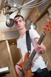 Bajista joven que se coloca con su guitarra Fotografía de archivo