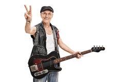 Bajista punky mayor que hace un signo de la paz fotos de archivo
