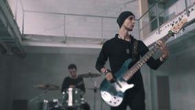 Bajista y guitarrista que juegan en un cuarto inacabado Paisaje industrial Dúo fresco de la roca del funcionamiento almacen de metraje de vídeo