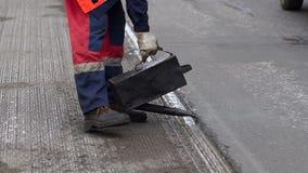 Bajo construcci?n Trabaje los detalles, trabajadores vierten la superficie de la carretera de la resina para cubrir el asfalto almacen de video