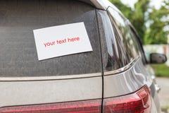 Bak av den smutsiga bilen med tomt papper för text Biltvättconcep Arkivfoton