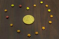 Bak av det guld- bitcoinmyntet i färgrika sockerstjärnor royaltyfria foton