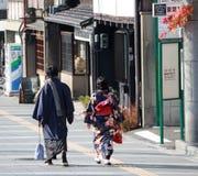 Bak av japansk man i Yukata för män och kvinnan i kimonoklänning som går på gångbanan Royaltyfri Foto