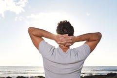 Bak av mannen som ser havet med händer bak huvudet Fotografering för Bildbyråer