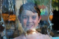 bak den lyckliga vattenfallet för pojke Arkivfoto