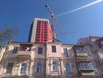 Bak det gamla huset byggs ett nytt ljust höghus arkivfoton