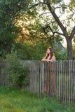 Bak ett lantligt staket är en ensam ung kvinna i en byklänning på skymning royaltyfri bild