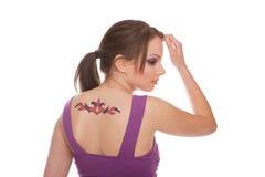 bak henne tatueringkvinnan Arkivfoto