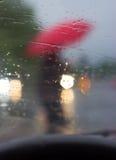 Bak hjulet - kontur av en man med det röda paraplyet Royaltyfri Foto