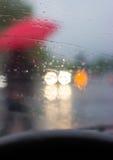 Bak hjulet - kontur av en man med det röda paraplyet Fotografering för Bildbyråer