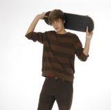 bak huvudet hans holdingskateboardtonåring arkivbild