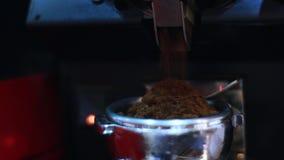 Bak kaféstång häller kaffekvarnen jordkaffe i hållare arkivfilmer