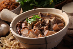 Bak kuh teh. A Malaysian herbal pork dish with herbs and rice as background Royalty Free Stock Photography