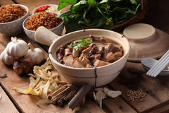 Bak kuh teh. A Malaysian herbal pork dish with herbs and rice as background Royalty Free Stock Images