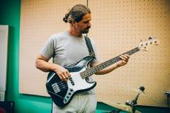 Bak plats Gitarristövning som spelar gitarren i smutsig musik s Arkivbilder
