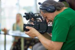 Bak platserna av filmskytte- eller videoproduktion och filmbes?ttningen team med kamerautrustning p? utomhus- l?ge royaltyfria foton