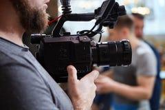 Bak platserna av filmskytte- eller videoproduktion och filmbes?ttningen team med kamerautrustning p? utomhus- l?ge royaltyfri fotografi