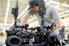 Bak platserna av filmskytte- eller videoproduktion och filmbes?ttningen team med kamerautrustning p? utomhus- l?ge royaltyfri foto