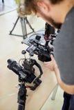 Bak platserna av filmskytte- eller videoproduktion och filmbes?ttningen team med kamerautrustning p? utomhus- l?ge arkivfoton