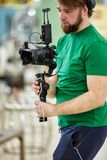 Bak platserna av filmskytte- eller videoproduktion och filmbes?ttningen team med kamerautrustning p? utomhus- l?ge fotografering för bildbyråer