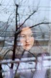 bak SAD fönster för flicka arkivfoto