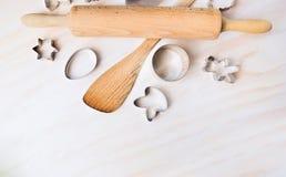 Bak tol en Pasen-koekjessnijders op witte houten achtergrond, hoogste mening stock afbeeldingen