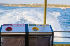 Bak voor Huisvuil in rood en recycling in geel op het achtergedeelte van een veerboot stock foto's