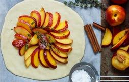 Baka en mördegstårta med persikor, nektariner Ingredienserna på tabellen - deg, persikor, nektariner, socker, kanel, timjan Royaltyfri Fotografi