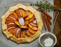 Baka en mördegstårta med persikor, nektariner Ingredienserna på tabellen - deg, persikor, nektariner, socker, kanel, timjan Royaltyfri Foto