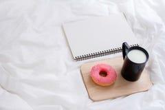 Baka ihop donuts med en kopp av mjölkar på säng Arkivbild