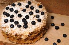 Baka ihop i lager Napoleon med bärblåbäret på ett grovt trämagasin, stänk med pudrat socker för menykafé Royaltyfri Foto