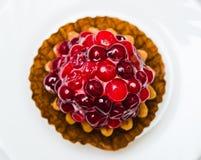 Baka ihop med en tranbär på en vit platta Royaltyfri Bild