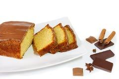 Baka ihop med glasyr av isolerade choklad och kryddor på vit Royaltyfri Bild