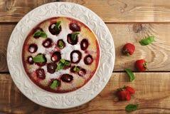 Baka ihop med jordgubbar i platta på träbakgrund Royaltyfri Fotografi