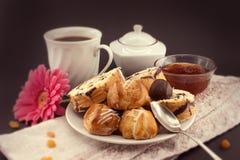 Baka ihop rulle och eclairen på plattan med kaffe på mörk bakgrund Royaltyfri Bild
