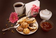 Baka ihop rulle och eclairen på plattan med kaffe på mörk bakgrund Royaltyfri Foto