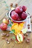 Baka med äpplen och muttrar Arkivbilder