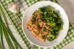 Bakad öring som tjänas som med kokt broccoli arkivfoton