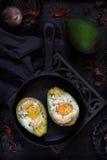 Bakad avokado med ägget på en mörk bakgrund Royaltyfri Fotografi