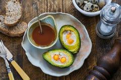 Bakad avokado med vaktelägg Arkivfoto