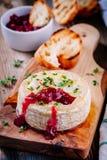 Bakad camembert med tranbärsås och timjan arkivbild