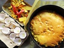 Bakad charlotte paj samman med ingredienser - tom äggskal och hud av ett äpple royaltyfri foto